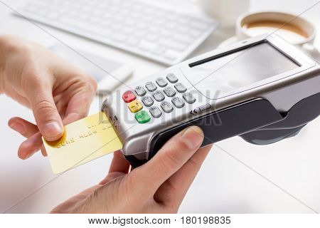 Payment by card in cafe with keyboard and coffee on white desk background