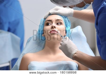 Plastic surgeon making facial injection in clinic