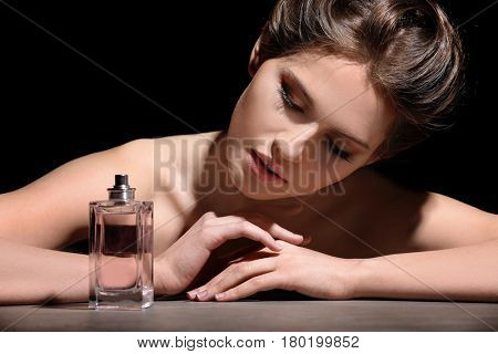 Beautiful young woman with bottle of perfume on dark background, closeup