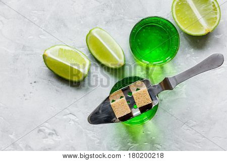 absinthe shots with fresh green lime slices and sugar cubes on stone bar table background top view