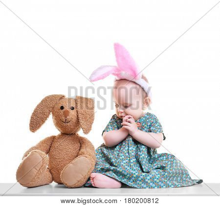 Cute funny baby with bunny ears and cuddly toy on white background