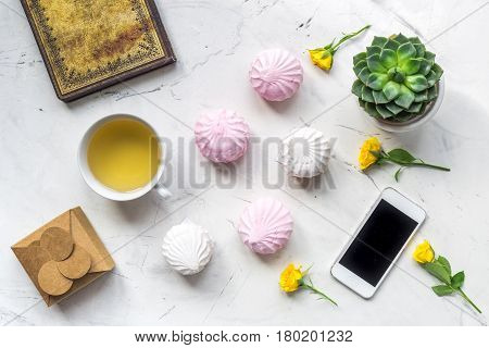 modern home office with flowers, mobile, tea, marsh-mallow and copybook in spring concept on light marble desk background top view