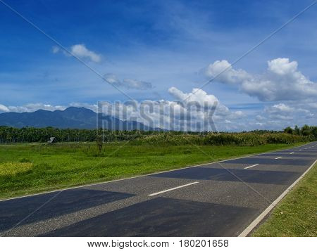 Summer landscape with road through rural land. Tropical nature bright view from highway. Exotic island travel panorama with sunny roadside. Tourism and vacation banner template with place for text