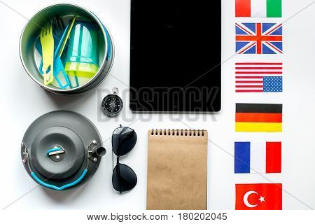 Outfit for trip with flags and tablet on white table background top view