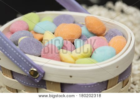 Easter gummy egg candies in pink blue orange yellow purple pink and green in a basket