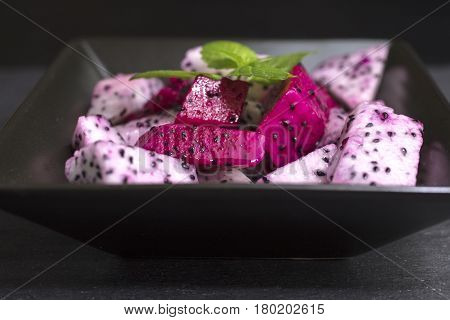 White and Red Dragon Fruit Salad sliced in a Black Ceramic Bowl