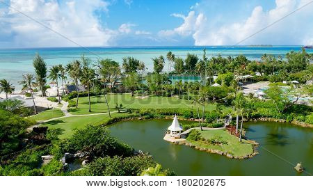 Landscaped gardens Pristine blue waters of the Micro Beach and the far-off Managaha Island backdrops a perfectly manicured garden with pond in Saipan, Northern Mariana Islands.