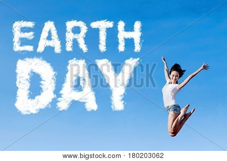 Young woman leaps on the sky with cloud shaped Earth Day text. Concept of Earth Day