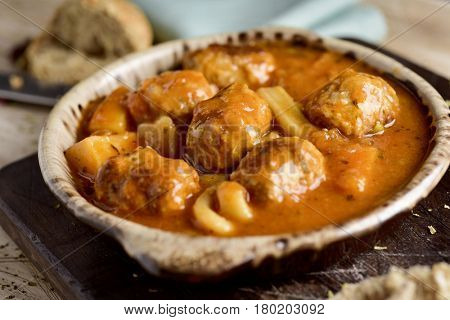 closeup of an earthenware bowl with typical spanish albondigas con sepia, meatballs with cuttlefish, on a rustic wooden table