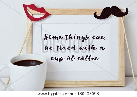 a wooden-framed picture with the text some things can be fixed with a cup of coffee written in it, a red mouth and a mustache attached to sticks and a cup of coffee on a white surface