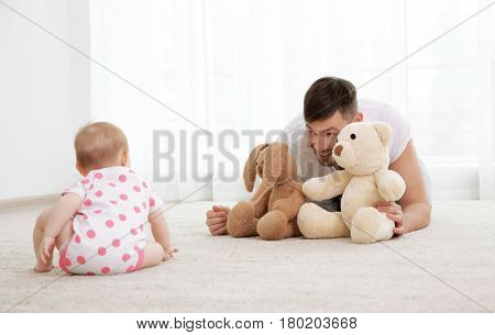 Father lying with cute baby daughter on carpet at home