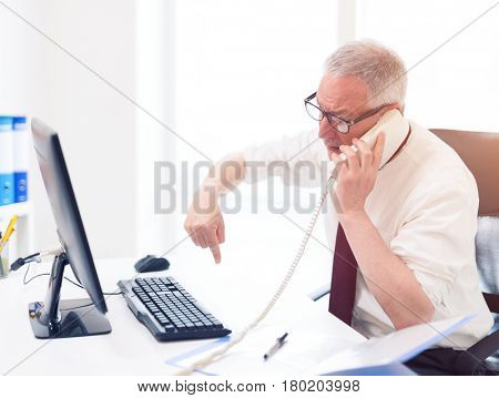 Angry business man talking on the phone