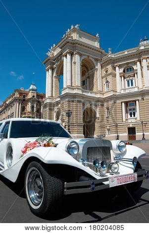 Odessa, Ukraine, 26 july 2009 - retro limousine decorated with flowers waiting wedding ceremony, old palace named opera theater on background, famous touristic place at center city