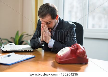 Desperate businessman waiting for a phone call
