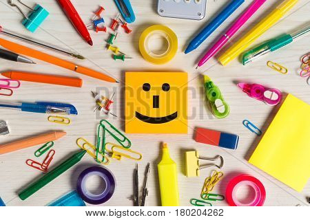 Smiling note emoticon and stationery around it
