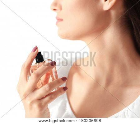 Beautiful young woman with bottle of perfume on light background