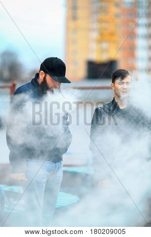 Vape. Two Young People Stand And Smoke Electronic Cigarettes In The Street On A Cloudy Day. Lifestyl