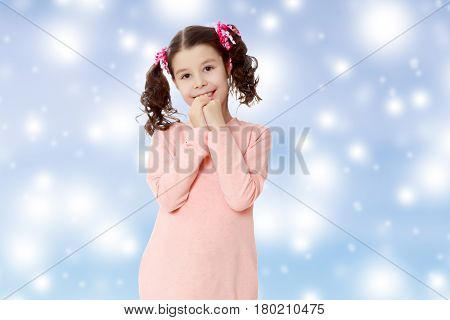 Cute little girl with long curly tails on the head, in which braided red ribbons . In long pink dress. The girl shyly holding hands near the face.Blue Christmas festive background with white snowflakes.