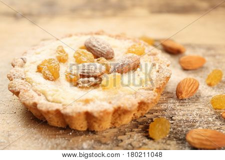 Delicious crispy tart with sugar powder, almond and raisins on table, closeup
