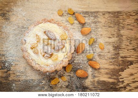 Delicious crispy tart with sugar powder, almond and raisins on wooden table