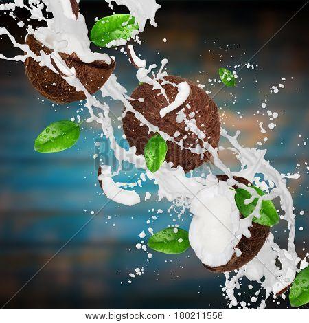 Coconuts with milk splash over vintage wooden background. Freeze motion.