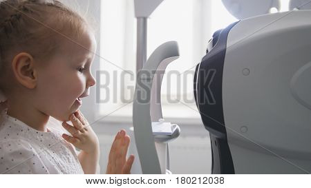 Children ophthalmology - optometrist Checks Child's Eye, telephoto