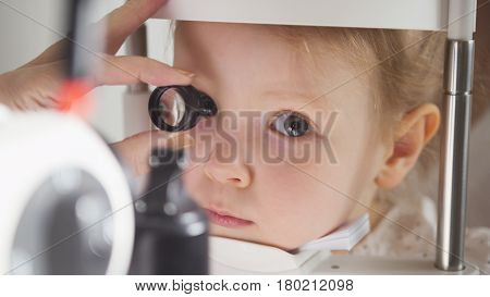 Child's ophthalmology - doctor optometrist checks eyesight for little girl , close up