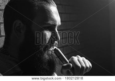 Vape. Young Brutal White Guy With Large Beard And With Electronic Cigarette. Black And White Photo.