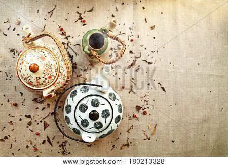 3 various traditional ceramic teapots on a canvas background with copy space. Group of cute steaming clayware pots with hot tea among tea leaves and berries scattered on fabric