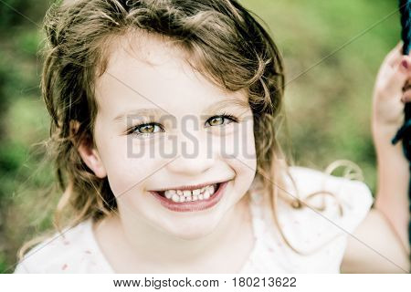 Beautiful happy young girl on a swing