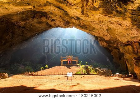 Morning sunbeam on golden buddhist pavilion in wild cave Sam Roi Yot Thailand