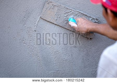 Man worker Plastering concrete with the wall and The building with concrete for house construction.