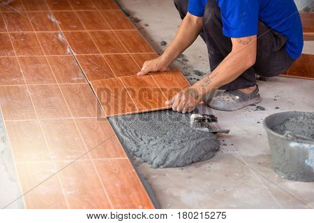 Man worker Tiler install ceramic tiles on a floor concrete