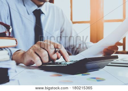 Businessman analyzing investment charts with calculator on office desk table.Close up.Financial Report Revenue Statistical Accounting Concept.