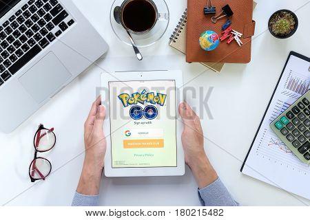 CHIANGMAI THAILAND -FEB 052017:Man hand holding ipad 4 with busy page of popular app Pokemon Go