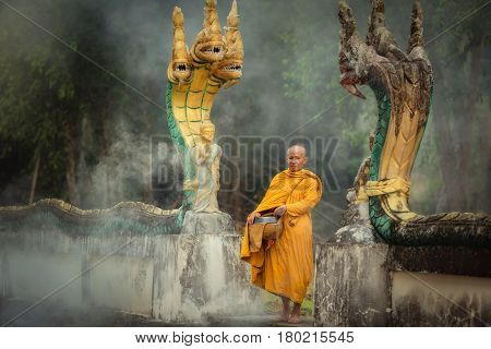 Naga Statue with Monk alms round in the temple