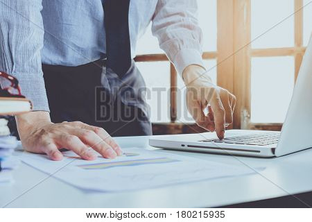 Businessman hand using and working with modern laptop computer on office desk table close up.Business concept.