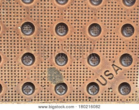 Weathered street steel cover plate with three letters reading  USA in a right lower corner