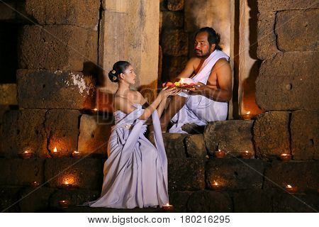 Priest or Yogi and Woman priest are Religious ceremony in Ancient ornate huts made of stone or archaeological sites.