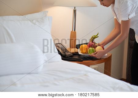 Maid putting plate with fresh fruits on bed table