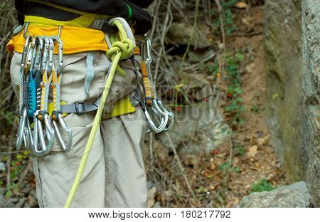 A rock climber in the mountains ready to conquer the peaks with equipment.