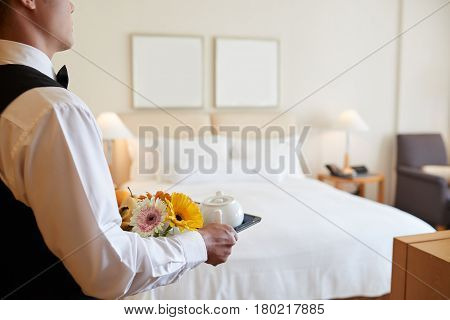 Waiter bringing tray with breakfast to the room