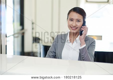 Portrait of pretty Asian female receptionist having phone call