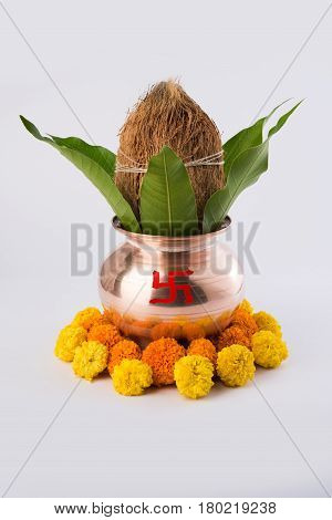 copper kalash with coconut and mango leaf with floral decoration. essential in hindu puja, selective focus, over plain background