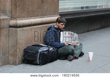 NEW YORK - APRIL 4, 2017: Homeless man in front of Macy's store in Midtown Manhattan