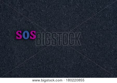 Wooden letters on the black surface empty space on the right the word sos