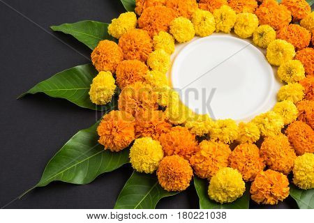 flower rangoli made using marigold or zendu flowers and mango leaves over black background with copy space in the middle, selective focus