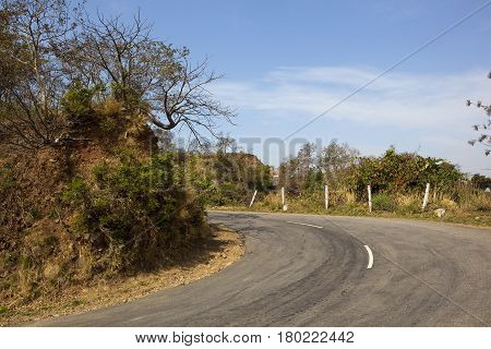a hairpin bend in the road going through morni hills nature reserve near chandigarh in india with vegetation and trees under a blue sky