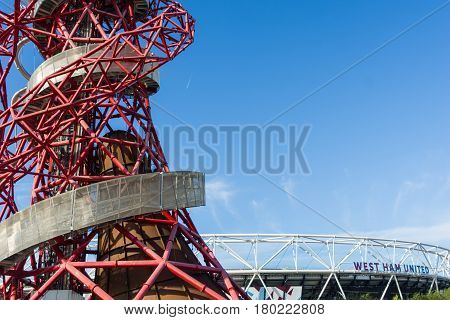 London, England - October 17, 2016;  ArcelorMittal Orbit abstract red tubular spiralling steel structure on right with silver outer walkway at 114.5 metre London's tallest sculpture a popular tourist attraction and observation tower in the Queen Elizabeth