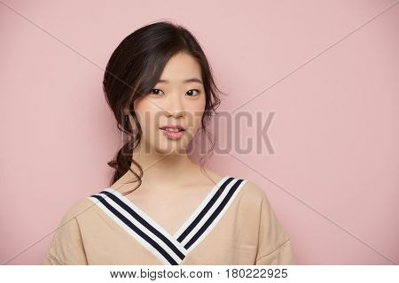 Young beautiful Korean girl smiling at camera, isolated on pink